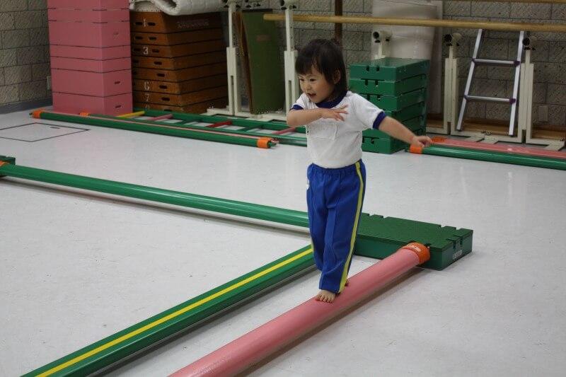子どもがビームを立って渡る運動遊び