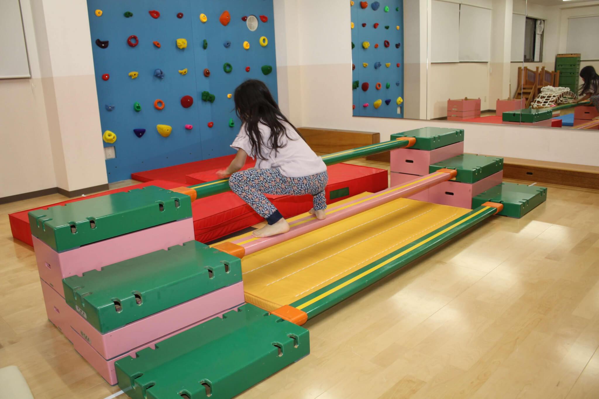 子どもがくまになりきってビームを横断する運動遊び