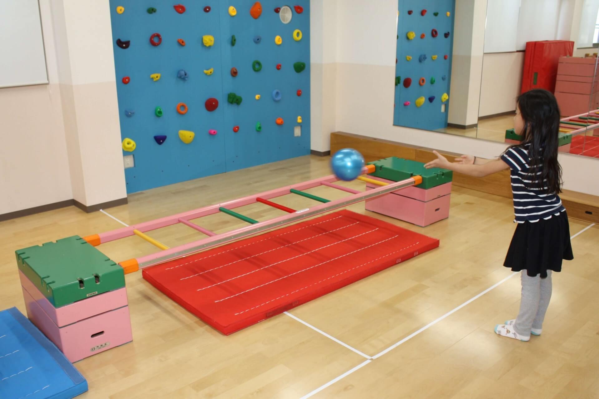 子どもがはしごに向かってボールを投げる運動遊び