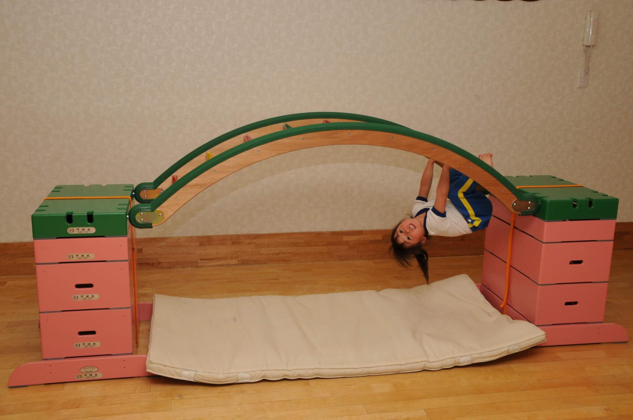 子どもが巧技台丸型はしごにぶら下がっている遊ぶ画像